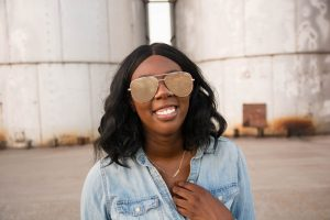 Tasha Robinson Imperfect Concepts wearing: Sunglasses: Quay X Desi, Shirt: Target, Jeans: American Eagle, Shoes: Charlotte Olympia and Bag: Balenciaga
